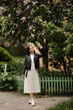 Beautiful model girl in a white midi skirt and black leather jacket posing near a bloomy lilac tree. Young brunette woman in spring outfit posing outdoors