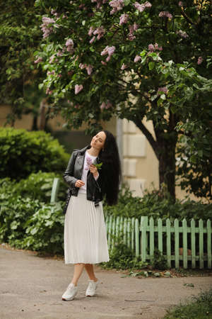 Young model woman in white skirt and black leather jacket is enjoying blooming lilac tree on the spring day