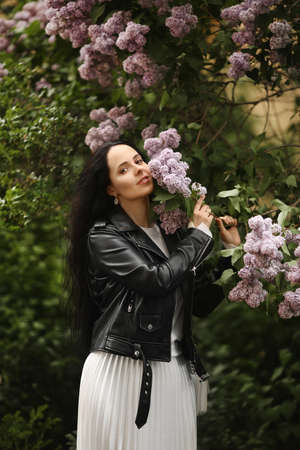 Young model woman in spring outfit is enjoying blooming lilac tree on the spring day