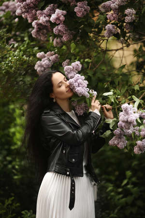 Beautiful young woman in leather jacket enjoying the smell of the bloomy lilac tree in springtime