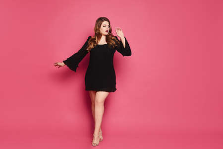 Plus size model girl in black gown makes step up on the pink background