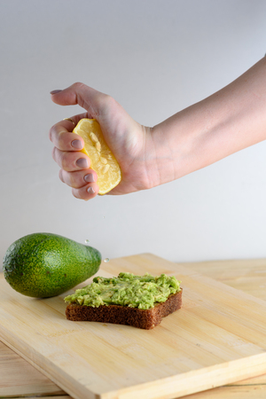 Woman preparing delicious avocado toast over wooden table, squeezing half of lemon on whole bread avocado toast. Beautifully rye bread with smashed green avocado on a board and white background.