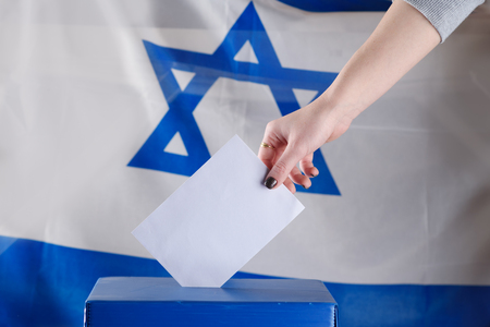 Israeli woman votes at a polling station on election day.Close up of hand with white votes paper on Israel flag background. Mocup, space for text.