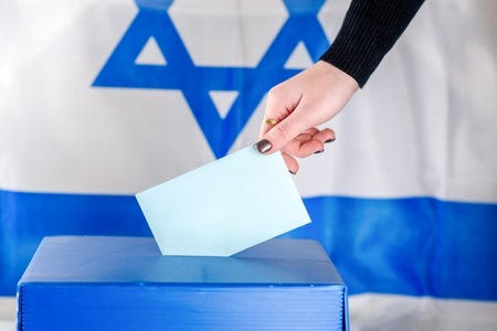 Israeli Young woman putting a ballot in a ballot box on election day. Close up of hand with white votes paper on Israel flag background. Mockup, space for text.