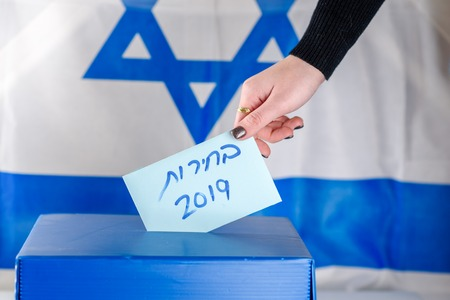 Israeli woman votes at a polling station on election day.Close up of hand. Hebrew text Elections 2019 on Israel flag background. Israeli legislative Elections for the 21st Knesset Israel 9 April 2019 Stock Photo