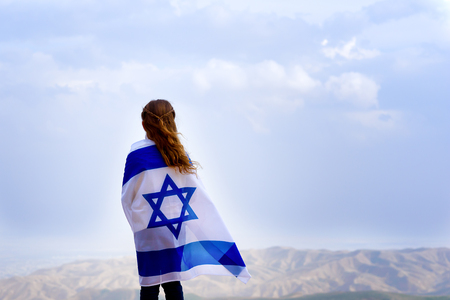 Little patriot jewish girl standing and enjoying great view on the sky, valley and mountains with the flag of Israel wrapped around her. Memorial day-Yom Hazikaron and Yom Haatzmaut concept. Foto de archivo