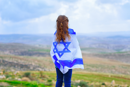 Little patriot jewish girl standing and enjoying great view on the sky, valley and mountains with the flag of Israel wrapped around her. Memorial day-Yom Hazikaron and Yom Haatzmaut concept. 写真素材
