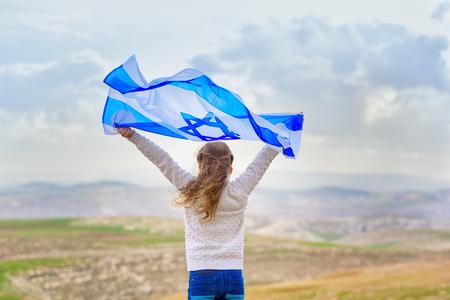 Mała żydowska dziewczyna patriota stojąc i ciesząc się z flagą Izraela na tle błękitnego nieba. Dzień Pamięci Yom Hazikaron, patriotyczne święto Dzień Niepodległości Izrael - koncepcja Yom Haatzmaut