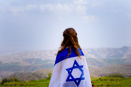 Little patriot jewish girl standing and enjoying great view on the sky, valley and mountains with the flag of Israel wrapped around her. Memorial day-Yom Hazikaron and Yom Haatzmaut concept. Imagens