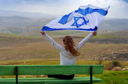 Beautiful young jewish girl sitting holding Israel flag in the wind and enjoying great view landscape on the sky, field and mountains.Patriotic holiday. Independence day Israel - Yom Haatzmaut .