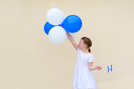 Happy kid, cute little caucasian girl, age 8-9 with blue and white balloons ans Israel flag. Patriotic holiday Independence day Israel - Yom Haatzmaut concept.Copy space for text. 写真素材