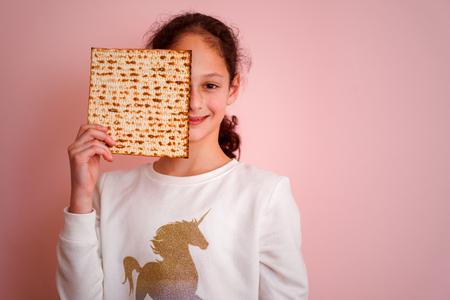 Portrait of the cute teenager girl holding matzah. Jewish child eating matzo unleavened bread in Jewish holidays Passover. Stockfoto