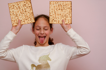 Portrait of the cute teenager girl holding matzah and shows tongue. Jewish child eating matzo unleavened bread in Jewish holidays Passover.