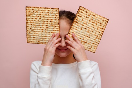 Portrait of the cute teenager girl holding matzah. Jewish child having fun and eating matzo unleavened bread in Jewish holidays Passover. Stock Photo