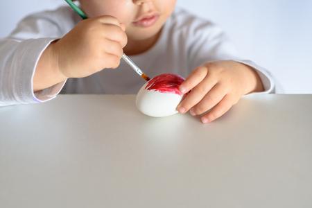 Happy easter. Funny little girl painting Easter eggs. Happy toddler preparing for Easter.