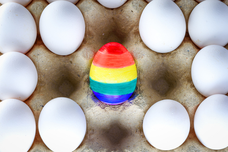Egg with rainbow colors of the LGBT flag standing out from crowd of plenty identical white eggs in carton box. LGBT community and Pride Month concept.