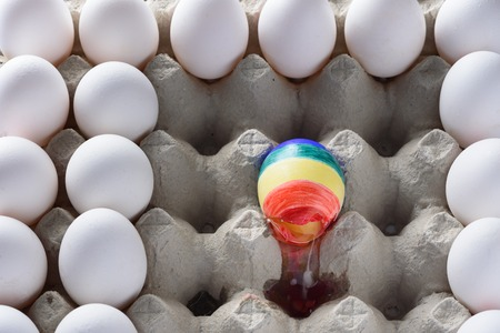 Broken egg with the colors of the LGBT flag surrounded of white other many eggs  in carton cage. International Day Against Homophobia concept. 写真素材