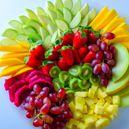 Fruit platter with fresh grapes, apple, pineapple, kiwi, mango, red ripe strawberry and pitaya. Excellent idea for Mishloach Manot: Jewish ritual of Sending Food Gifts on Purim.Colorful Fruit tray. Banque d'images - 122324155