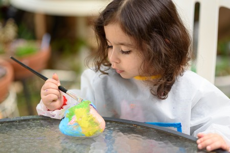 Portrait of little child painting, summer outdoor.Kid drawing on a stone. Imagens