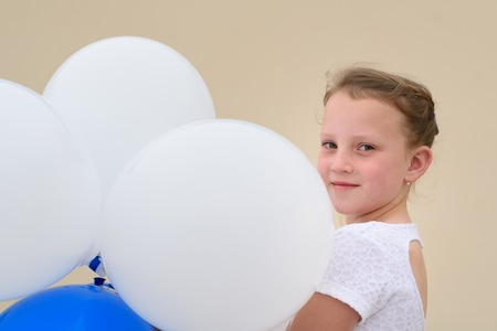 Little girl playing with balloons outdoor. Happy child wears white summer dress.Summer vacation,holidays, celebration, children and people concept. Imagens