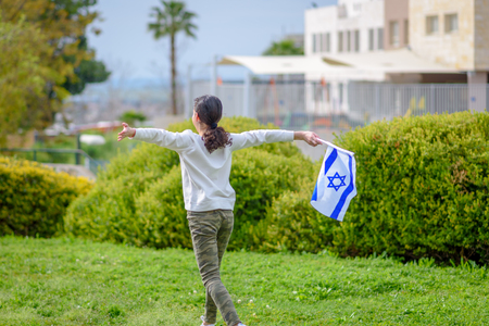 Happy Girl running with Israel flag. Image to illustrate election win, patriotic holiday Independence day Israel - Yom Haatzmaut concept.