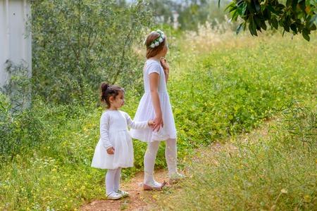 세로 사랑스러운 작은 아이 야외. 손을 잡고 있는 어린 아이들. 사랑에 빠진 여름.