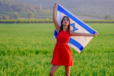 Young woman patriot jewish proud girl standing with flag of Israel on amazing landscape in beautiful summer or spring day. Memorial day-Yom Hazikaron, Independence day Israeli - Yom Haatzmaut concept