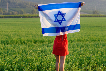 Back view Young woman patriot jewish girl standing with flag of Israel on amazing landscape in beautiful summer.Memorial day-Yom Hazikaron, Patriotic holiday Independence day Israel - Yom Haatzmaut