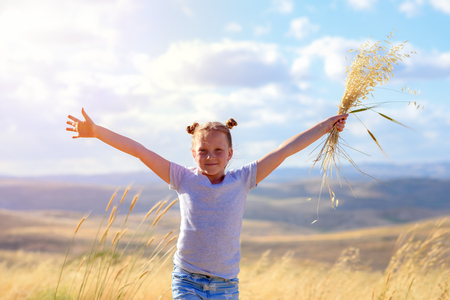 Happy little girl walking in golden wheat, holding spikes of wheat and ears of oats. Nature beauty, blue sky, white clouds and field of wheat.
