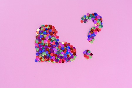 Creative image holographic glitters heart shape and question mark from sequins. Love symbol heart on pink background.