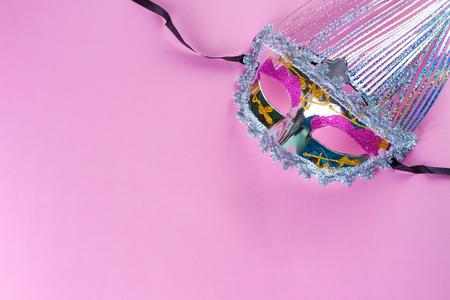 Holographic glittering carnival mask on pink background.Beautiful elegant venetian mask. Stock Photo