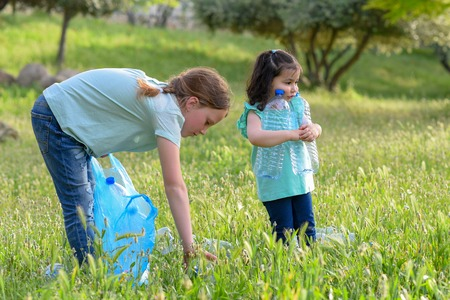 Two kids volunteer cleaning plastic pollution in summer park. Children with garbage bags cleaning up polluted environmental rubish in forest. Stock Photo