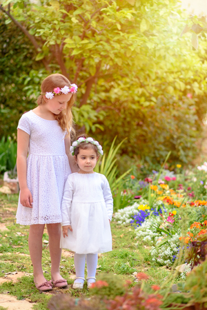 Two happy multiracial children with white dress and flower wreath playing outdoors. Kids having fun in summer or spring park. Beautiful girls on colorful nature background. Archivio Fotografico