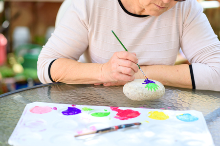 Happy authentic senior woman sitting outdoors at table painting pictures on stone.