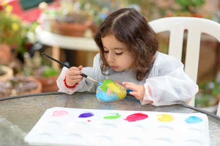 Portrait of little child painting, summer outdoor.Kid drawing on a stone. Reklamní fotografie