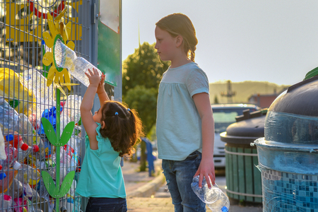 Little Girls Recycling Plastic Water Bottles in Yellow Metal Recycling Cage. Children Puts Plastic Waste in Recycling Bins in Street of City. Stock Photo
