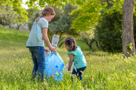 Le bambine prendono le bottiglie di plastica dall'erba. Bambini che raccolgono i rifiuti nel parco.