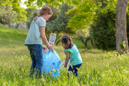 Małe dziewczynki bierze plastikowe butelki z trawy. Dzieci zbierające śmieci w parku.