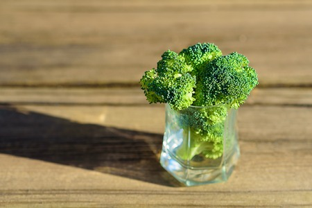 Healthy Green Organic Raw Broccoli Florets Ready for Cooking. Bunch of fresh green broccoli in glass on wooden table close up on the background of a stone wall. Stockfoto