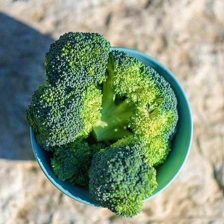 Healthy Green Organic Raw Broccoli Florets Ready for Cooking. Bunch of fresh green broccoli in bowl on rustic outdoor background of a stone table. Top view.