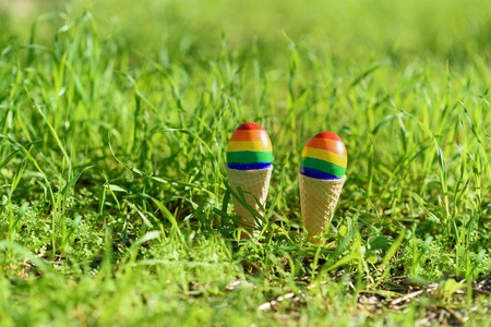 Lgbt couple family. Eggs with lgbt flag color in ice cream waffle cone on nature spring outdoor background. Creative idea for illustration gay parade, lgbt party, homosexual marriage, valentines day.