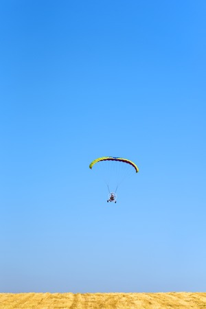 Powered paraglider parachute against blue sky and yellow field. Paramotor  flying in sunny day. Freedom and summer holiday concept, extreme sport.