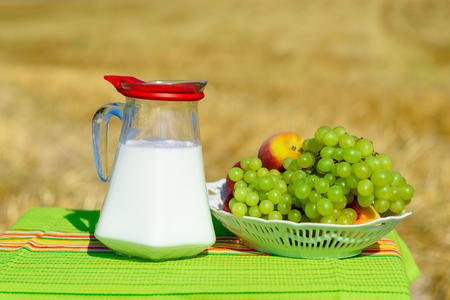 First fruits habikkurim in hebrew and jug of milk on wooden table with rustic fabric towel.Symbols of jewish holiday - Shavuot. Grapes and peaches on plate outdoor on the gold wheat field background.