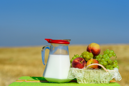 First fruits habikkurim in hebrew and jug of milk  on table with rustic fabric towel.Symbols of jewish holiday - Shavuot. Grapes and peaches on dish outdoor on the gold wheat field and sky background.