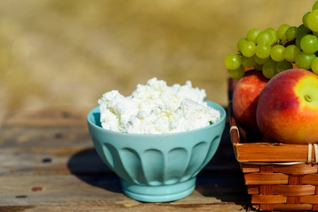 Close up Cottage cheese, and first fruit basket on wooden table over wheat field background. Jewish holiday Shavuot celebration, harvest festival, healthy breakfast, happy sunny day moments concept.