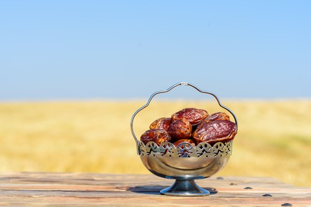 Dates on wooden table over field and sky background. Festive still life with copy space. Healthy vegan sweet food.
