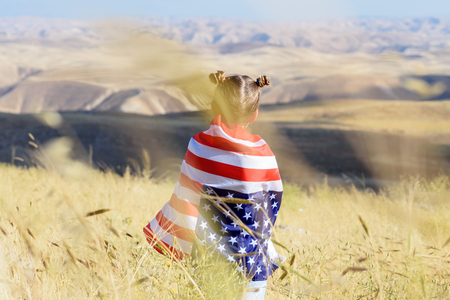 American flag. Back view little patriotic happy girl wrapping in usa national flag on beautiful landscape background. Patriotic child on wheat field. National 4 july. Memorial day.