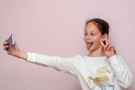 Young brunette girl, making selfie, showing v-sign and tongue out, funny face, posing at pink background. Soft focus on face of child. Фото со стока