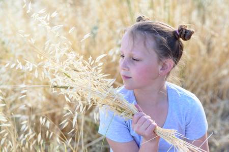 Beautiful girl holding spikes of wheat and ears of oats. Cute child sitting on the gold autumn field ready for harvest.