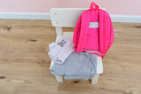 School supplies : bag and clothes in children girl room on white wood chair. Mom or parents preparing outfit for daughter to wear on their first day of preschool.